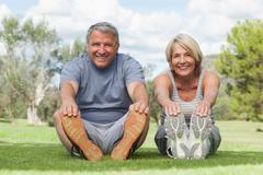 Stock Photo of Older couple stretching in the park