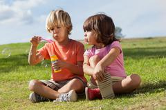 Little boy and girl blowing bubbles Stock Photos