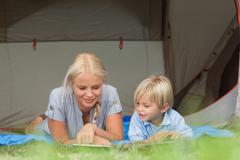Mother and son reading on a sleeping bag - stock photo
