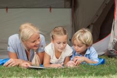 Mother and children reading on a sleeping bag - stock photo