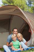 Portrait of son with parents on camping holiday - stock photo