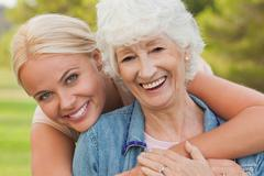 Portrait of elderly woman with her adult daughter - stock photo