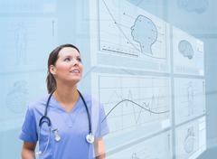 Nurse observing graphics on screen - stock photo