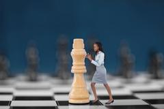 Businesswoman pushing chess piece Stock Photos