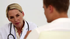 Concentrated female doctor listening to her patient - stock footage