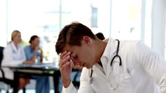 Young worried doctor holding his head Stock Footage