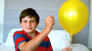 Stock Video Footage of Boy piercing his balloon in the bedroom