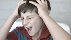 Annoyed boy holding his head between hands - stock footage