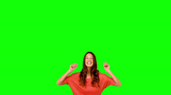 Woman jumping with arms raised on green screen - stock footage