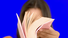 Woman flipping through a pink book on blue screen Stock Footage