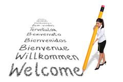 Businesswoman writing welcome in various languages with a giant pencil Stock Photos
