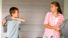 Young siblings having a pillow fight Stock Footage