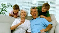 Grandparents and children raising their arms in the living room Stock Footage