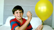Stock Video Footage of Boy piercing his yellow balloon and getting a fright