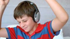 Young boy enjoying music with headphones Stock Footage