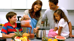 Woman with family pouring fruit cocktail from a blender Stock Footage