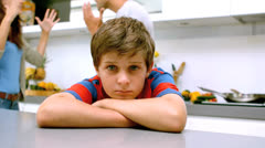 Sad boy with arms folded while parents quarreling Stock Footage