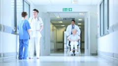 Multi Ethnic Staff Moving Patients Hospital Corridor Stock Footage