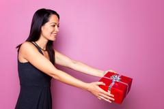 woman in a black dress giving a present - stock photo