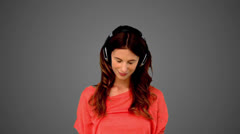 Woman listening to music on grey background Stock Footage