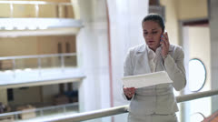 Angry businesswoman with cellphone in the office hall, steadycam shot Stock Footage