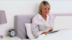 Mature woman using laptop in her bedroom Stock Footage
