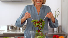 Smiling woman tossing her salad Stock Footage