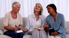 Three mature friends praying together - stock footage