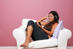 woman sat in an armchair listening to music - stock photo