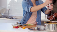 Woman putting salt and pepper in pot while cooking Stock Footage
