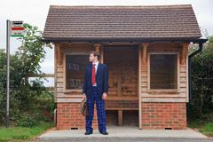 Businessman standing at a bus stop in pyjamas and slippers Stock Photos