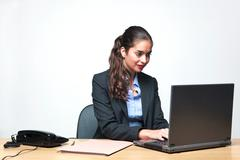 businesswoman sat at her desk typing on a laptop - stock photo