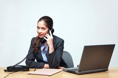 businesswoman sat at a desk on the telephone - stock photo