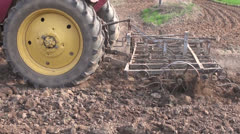Agriculture tractor plowing spring farm field with harrow Stock Footage