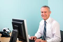 mature businessman sat at his office desk - stock photo