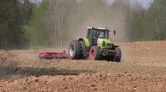 Big tractor plowed early spring farm field Stock Footage