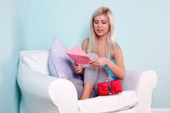 blond woman opening a birthday card - stock photo