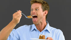 Man savouring a delicious cake on grey screen Stock Footage