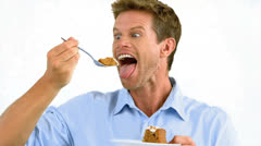 Man savouring a delicious cake on white background Stock Footage