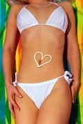 Woman sunbathing in white bikini with suntan lotion heart Stock Photos