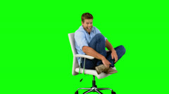 Smiling man cheering and turning on swivel chair on green screen Stock Footage