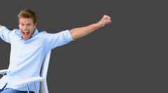 Man on swivel chair raising arms to show his success on grey screen Stock Footage