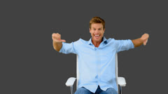 Man on swivel chair giving thumbs up on grey screen Stock Footage