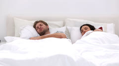 Couple sleeping peacfully with partner pressing snooze Stock Footage