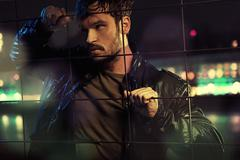attractive man behind metal fence - stock photo