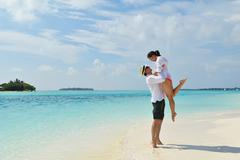happy young couple have fun on beach - stock photo