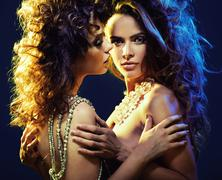 two curly-haired ladies in sexy hug - stock photo