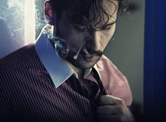 smoking serious man after tiring job - stock photo