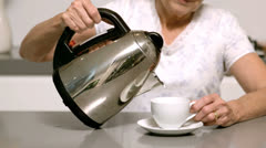Woman pouring hot water from kettle into cup Stock Footage