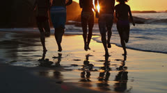 Silhouettes of friends running into the sea Stock Footage